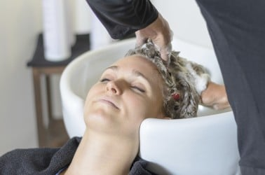 Vrouw ontspant bij de kapper tijdens wasbeurt