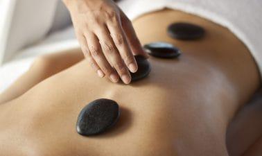 Hand van een therapeut die hot stones bij iemand op de rug legt.