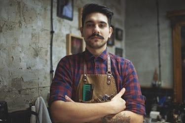 barbier met armen over elkaar en kappers benodigdheden in zijn schort