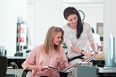 blond vrouw vraagt raad aan kapper over haarkleuringen