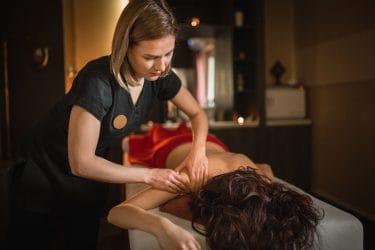 massagetherapeute geeft schoudermassage aan klant op een massagetafel