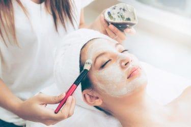 vrouw krijgt een gezichtsmasker aangebracht met kwast in beauty salon
