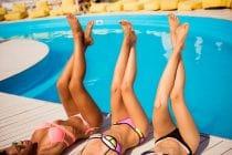 drie dames in bikini aan de rand van het zwembad die zomerse beauty behandelingen hebben ondergaan