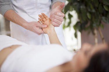 massagetherapeut geeft handreflexologie behandeling