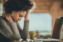 vrouw achter een computer met hoofdpijn en nekpijn