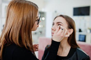 Visagiste brengt make-up aan bij jonge vrouw