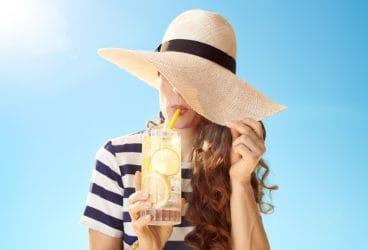 vrouw met cocktail verbergt haar witte huid onder grote zonnehoed