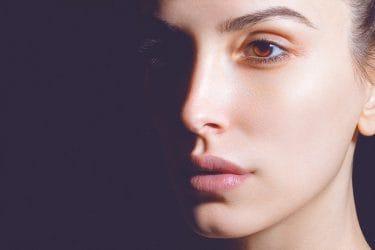 Vrouw met gezicht half in de schaduw en een mooi opgemaakt oog