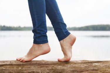 blote voeten lopen over een boomstam