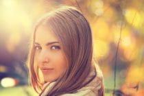Jonge vrouw tussen de herfstbladeren toont mooi verzorgde huid vanwege een goede beauty routine.