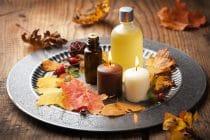 flesje etherische olie omgeven door herfstbladeren