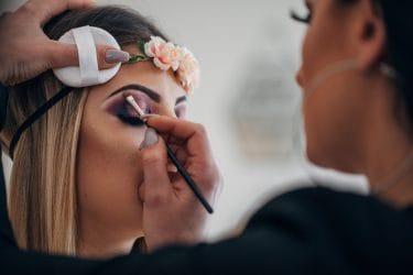Student van de opleiding make-up artist werkt aan een creatie.