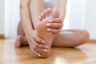 Vrouw pakt haar voet vast, vanwege pijn aan de voet. Wat kan de rol van voeding hierin zijn?