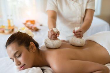 Vrouw ondergaat een verwarmende massage, namelijk een warme kruidenstempel massage