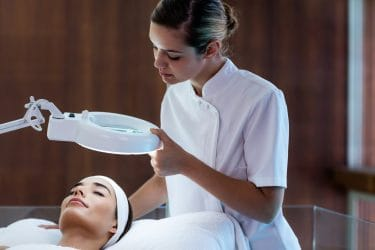 Schoonheidsspecialiste bestudeert huid van klant. Welke nieuwe behandelwijze is geschikt?