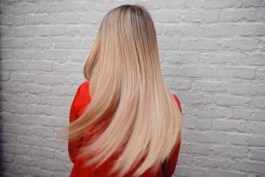 Blonde vrouw showt resultaat na een keratine haarbehandeling.