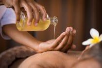 Massagetherapeut gaat massage geven met aromatische massageolie om een winterdip weg te masseren..