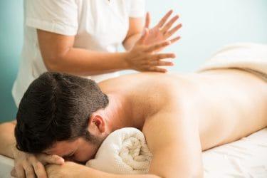 oefenen van massagetechnieken tijdens leren masseren via een online cursus. Tapotementen op de rug.