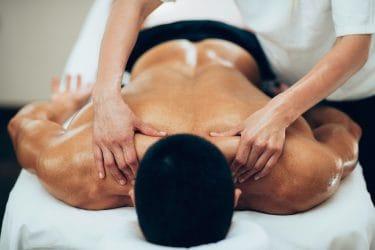 Man met overbelaste spieren ondergaat een sportmassage.