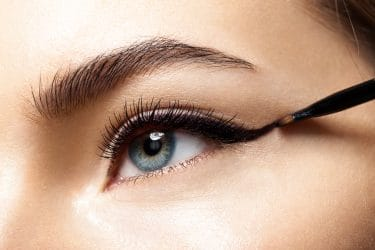 Vrouw met winged eyeliner als ideale make-up bij het dragen van een mondmasker.